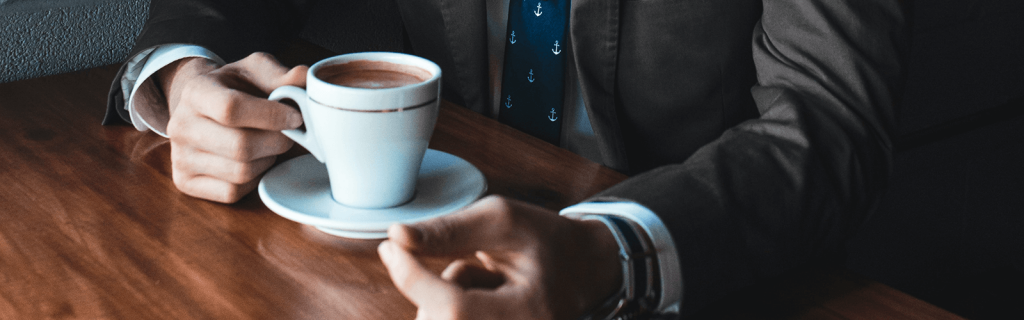 Business man with cup of coffee on table